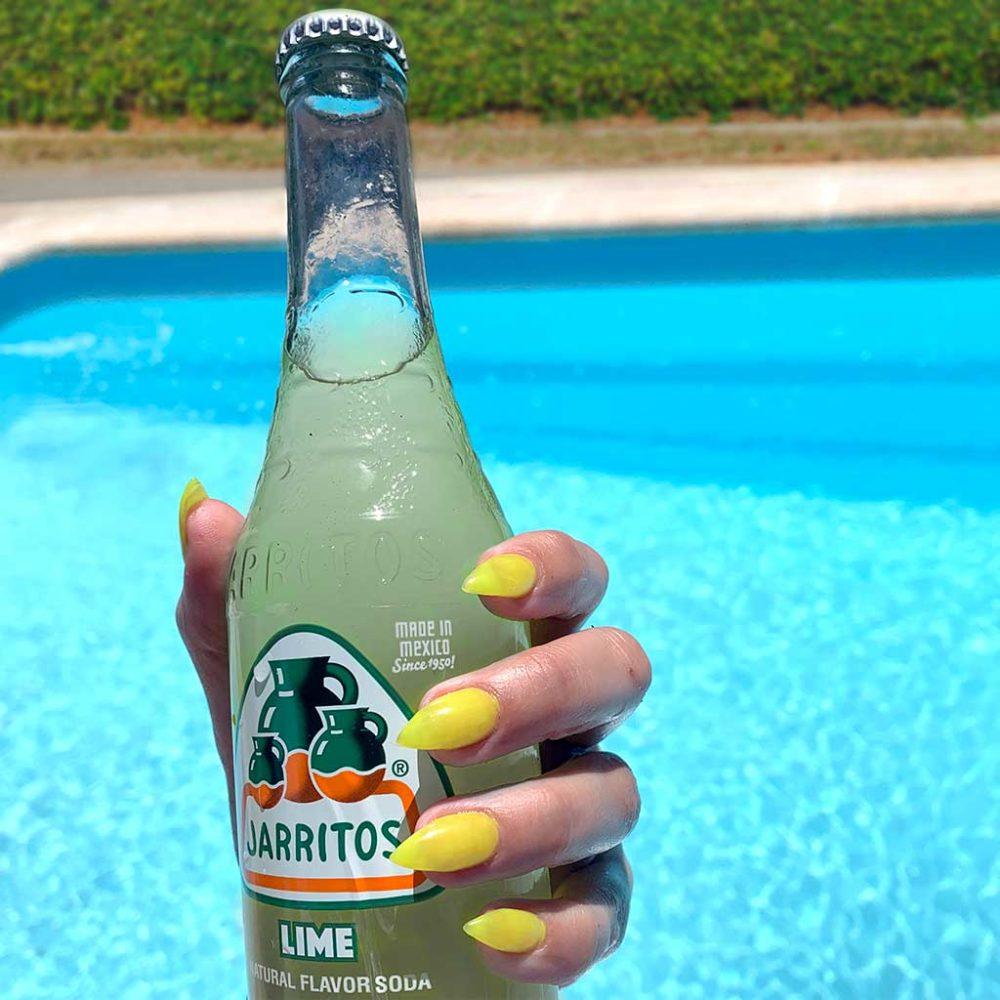 mano soteniendo un refresco de limón marca jarritos