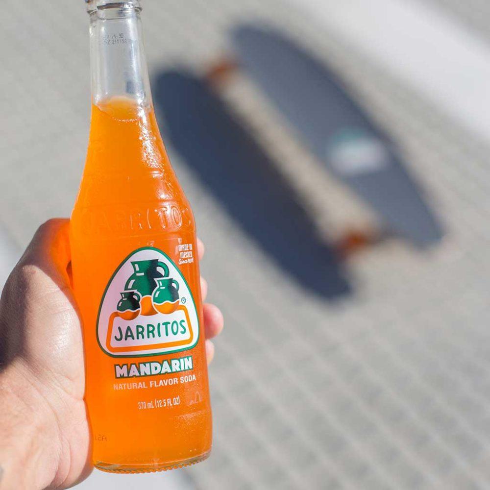 mano cogiendo un refresco sabor mandarina Jarritos