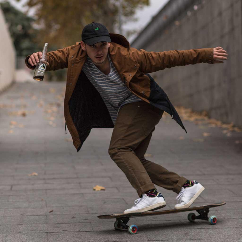 chico y su skateboard sosteniendo un refresco de cola marca Jarritos