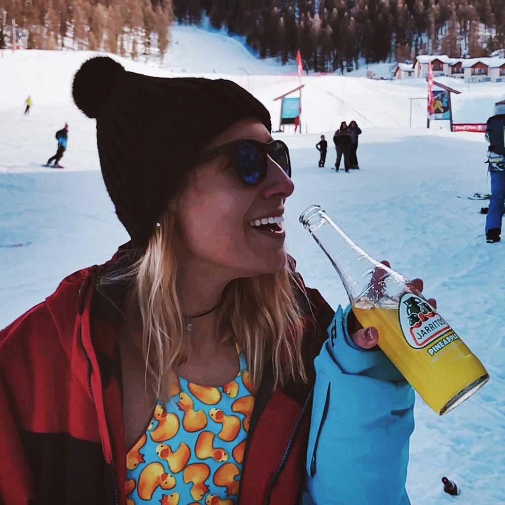 Chica feliz tomando refresco de piña Jarritos
