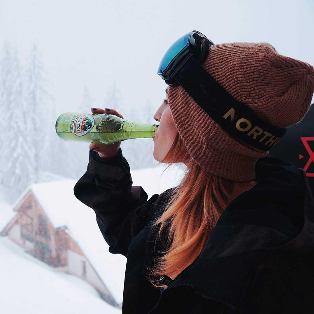 mujer bebiendo jarritos de torornja en la nieve